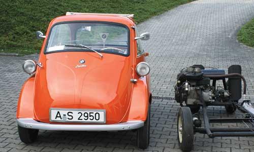 """Enthüllungsgeschichte: Eine """"Export"""" neben dem rollfähigen Chassis einer Isetta im Aufbau."""